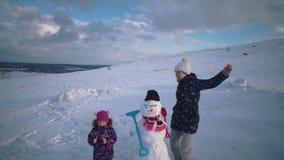 A mulher e a crian?a esculpem junto um boneco de neve no monte video estoque