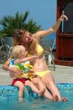 A mulher e a criança têm o divertimento na piscina Fotos de Stock Royalty Free