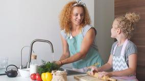 Mulher e filha bonito que cozinham na cozinha, fazendo a massa para a festa de anos filme