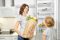 A mulher e a filha com produtos ensacam perto do refrigerador vazio imagens de stock