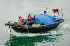 A mulher e a filha oferecem o fruto para a venda de seu barco na baía de Halong, Vietname Fotografia de Stock