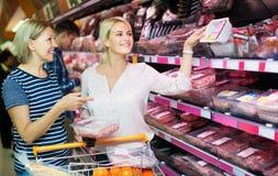 Mulher e filha que escolhem a carne Imagem de Stock