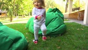 Mulher e filha que têm o divertimento em beanbags na natureza vídeos de arquivo