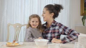 A mulher e a filha têm o divertimento durante o café da manhã video estoque