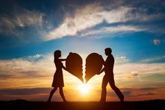 Mulher e homem com as duas metades de coração quebrado que vão ser juntado em um Amor fotografia de stock