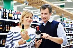 Mulher e homem com a garrafa do vinho na loja Fotografia de Stock