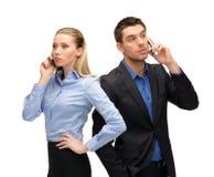 Mulher e homem com telefones celulares chamada Fotografia de Stock Royalty Free
