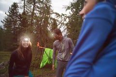 Mulher e homem de sorriso felizes com a lanterna elétrica do farol durante o nivelamento perto do acampamento Grupo de verão dos  imagens de stock