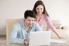 Mulher e homem felizes que usa o escritório do portátil em casa, documento fotos de stock