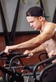 Mulher e homem que biking no gym, exercitando os pés que fazem cardio- bicicletas do ciclismo do exercício imagem de stock royalty free