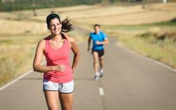 Mulher e homem que correm na estrada secundária Fotos de Stock