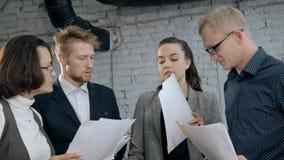 Mulher e homem que discutem o novo documento ou o contrato no escrit?rio video estoque