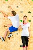 Mulher e homem que escalam na parede de escalada Fotos de Stock Royalty Free