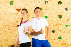 Mulher e homem que estão na parede de escalada Fotos de Stock