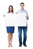 Mulher e homem que guardam um cartaz fotografia de stock
