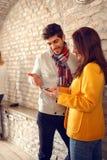 Mulher e homem que olham o telefone celular fotografia de stock royalty free