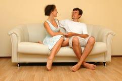 Mulher e homem que sentam-se no sofá branco fotografia de stock