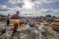 Mulher e homem que trabalham na praia perto do mercado de peixes longo de Hai Imagens de Stock