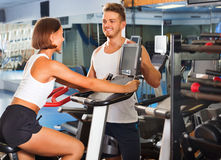 Mulher e homem que usa a maquinaria do gym da bicicleta junto Fotografia de Stock