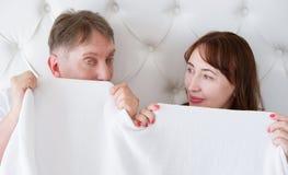 Mulher e homem superiores na cama Pares da Idade Média que encontram-se no quarto e que escondem sob a cobertura branca da placa  foto de stock