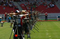 Mulher e homens que apontam a um alvo em uma competição do tiro ao arco fotografia de stock royalty free