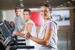Mulher e homens que correm na escada rolante na aptidão Imagens de Stock Royalty Free