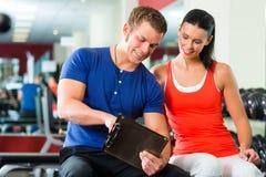 Mulher e instrutor pessoal no gym, com dumbbells