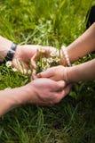 Mulher e mãos e ramalhete do homem dos camomiles na grama Fotografia de Stock Royalty Free