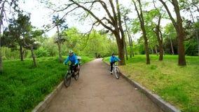 Mulher e menina em bicicletas no parque Movimento lento filme