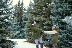 A mulher e a menina estão jogando com as bolas de neve na floresta do inverno, paisagem bonita com abeto nevados fotografia de stock