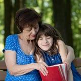 A mulher e a menina idosas estão sentando-se no banco, no abraço e no r Imagem de Stock Royalty Free