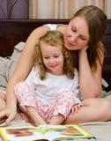 A mulher e a menina leram um livro Fotografia de Stock