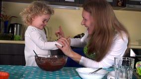 Mulher e menina loucas com as caras sujas do chocolate na cozinha vídeos de arquivo
