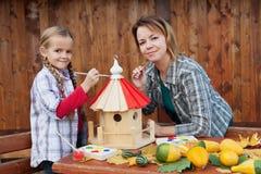 Mulher e menina que pintam uma casa do pássaro Fotografia de Stock Royalty Free
