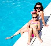 Mulher e menina que sentam-se perto da piscina fotografia de stock