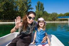 Mulher e menina que sorriem no borad em um barco Imagens de Stock