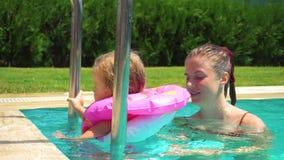 Mulher e menina que têm o divertimento na piscina video estoque
