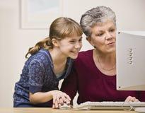 Mulher e menina que usa o computador imagem de stock