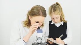 Mulher e menina que usa o microscópio filme