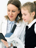 Mulher e menina que usa o microscópio Imagem de Stock