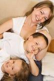 Mulher e miúdos no sofá Fotos de Stock Royalty Free