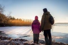 Mulher e moça que olham o por do sol bonito do inverno contra a água gelada e o céu azul Imagem de Stock Royalty Free