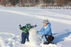 A mulher e a neve do lance do rapaz pequeno Imagem de Stock Royalty Free