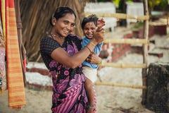 A mulher e o bebê indianos não identificados em seus braços estão sorrindo com muito fotografia de stock royalty free