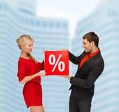 A mulher e o homem de sorriso com venda vermelha dos por cento assinam Imagens de Stock