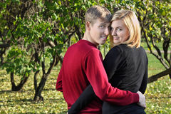 A mulher e o homem felizes abraçam e olham para trás no parque Fotos de Stock