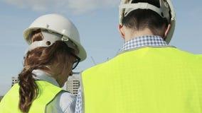 A mulher e o homem são os chefes de máquinas do projeto em vestes verdes video estoque