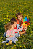 A mulher e os miúdos que jogam com um moinho de vento brincam Fotos de Stock Royalty Free