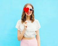 Mulher e pirulito de sorriso bonitos felizes do retrato sobre o azul colorido foto de stock royalty free