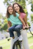 Mulher e rapariga em uma bicicleta que sorriem ao ar livre Imagens de Stock